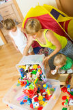 Children and mother collecting toys Royalty Free Stock Images