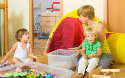 Children and mother collecting toys. Two little siblings and mother collecting toys in plastic box Stock Photos
