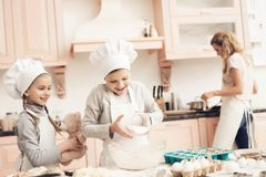 Children with mother in kitchen. Brother and sister are adding flour to dough. royalty free stock images