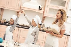 Children with mother in kitchen. Brother and sister are dancing, mother is holding cookbook. royalty free stock photo