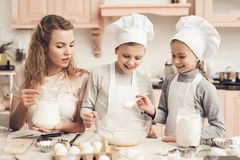 Children with mother in kitchen. Kids are adding flour and mother is adding milk in bowl. Children in chef`s hats with mother in kitchen. Kids are adding flour stock image