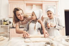 Children with mother in kitchen. Mother is helping kids to roll out dough. Children in chef`s hats with mother in kitchen. Mother is helping kids to roll out royalty free stock photos