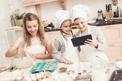 Children with mother in kitchen. Mother is putting dough in baking dish and kids are looking on tablet. Children in chef`s hats with mother in kitchen. Mother Stock Images