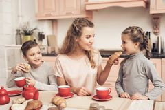 Children with mother in kitchen. Family is drinking tea with croissants. stock photo