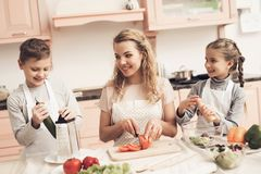 Children with mother in kitchen. Family is preparing vegetables for salad. stock photography