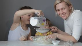 Children and mother knead the dough for cookies by hand stock video