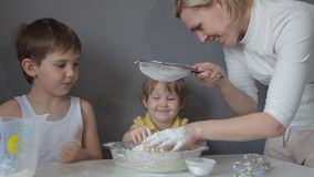 Children and mother knead the dough for cookies by hand stock video footage