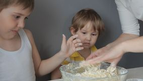 Children and mother knead the dough for cookies by hand.  stock video footage