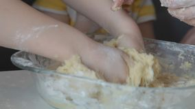 Children and mother knead the dough for cookies by hand.  stock footage