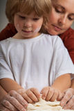 Children and mother and knead dough together Stock Image