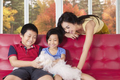 Children and mother playing puppy at home Stock Photography
