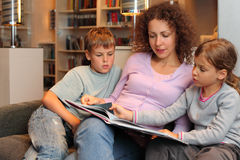 Children with mother sit on sofa and read book Royalty Free Stock Image
