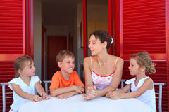 Children and mother sit on verandah round table Royalty Free Stock Images