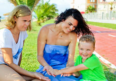 Children with mother sitting and laughing. Keep mom`s hand. Mother holds on hands her son, near smilling daughter. Happy family in summer vacation. Sincere Stock Photography