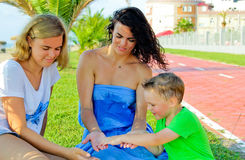 Children with mother sitting and laughing. Keep mom`s hand. Mother holds on hands her son, near smilling daughter. Happy family in summer vacation. Sincere Stock Images