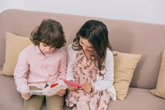 Children with mothers day greeting cards sitting on couch. At home royalty free stock photo