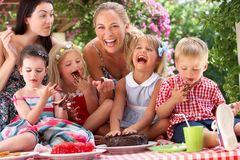 Children And Mothers Eating Cake At Outd. Children And Mothers Eating Jelly And Cake At Outdoor Tea Party Royalty Free Stock Image