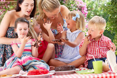 Children And Mothers Eating Cake At Outd. Children And Mothers Eating Jelly And Cake At Outdoor Tea Party Royalty Free Stock Photography
