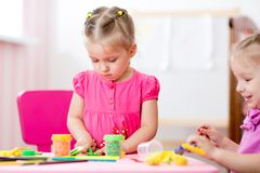 Children mould from clay in play room. Preschool Stock Images