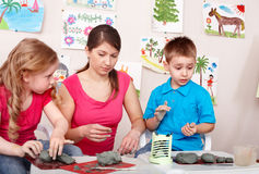 Children mould with teacher from clay. Child development Royalty Free Stock Images