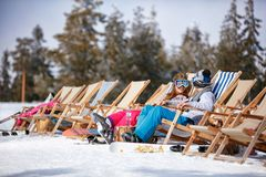 Children at mountains in winter laughing and relax in sunbed cha. Happy children at mountains in winter laughing and relax in sunbed chairs Stock Image