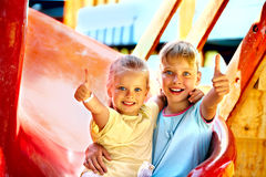 Children move out to slide in playground. Happy children move out to slide in playground Royalty Free Stock Photo