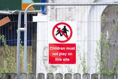 Children must not play on scaffolding at construction building site safety sign stock photo