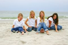 Children At Myrtle Beach. Four children - ages 1, 8, 10, 11, and 13 - sitting on the beach at Myrtle Beach, South Carolina Royalty Free Stock Photos