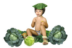 The children of the nature. The child sitting on cabbage leaves Royalty Free Stock Photography