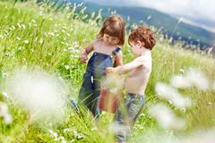 Children nature. Boy and girl in flowers Royalty Free Stock Image