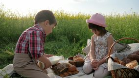 Children and nature, Friends on green lawn, picnic, boy and girl with food on nature, happy children in fresh air, boy stock footage