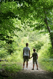Children on Nature Hike. Medium view of children holding hands while on a nature hike, framed by trees. Vertical format Stock Photo
