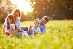 Children in nature make soap bubbles. Children in green nature make soap bubble on summer stock photos