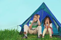 Children on nature, sit near tent and eat Stock Images