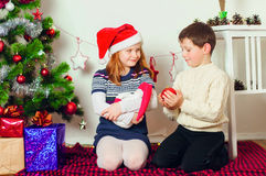 Children near a Christmas tree with gifts Royalty Free Stock Photos