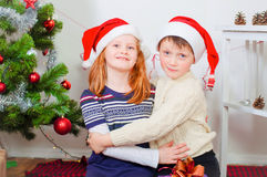 Children near a Christmas tree with gifts Stock Photo
