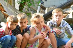 Children are near the ruined house, the concept of natural disaster, fire, and devastation. stock images