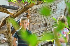 Children are near the ruined house, the concept of natural disaster, fire, and devastation. stock photography
