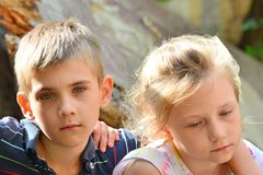 Children are near the ruined house, the concept of natural disaster, fire, and devastation. stock photo