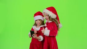 Children little ones show the tongue and make faces and make selfies on the smartphone. Green screen. Slow motion. Children in New Year costumes and red caps stock video