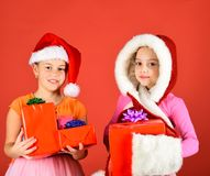 Children with nice faces stand on red background. Partying, holiday and xmas sale concept. Kids in Santa Claus hats with gift boxes open presents. Girls stock photo