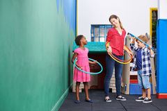 Children and nursery teacher with hula hoops Royalty Free Stock Image