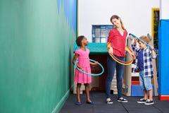 Children and nursery teacher with hula hoops. In kindergarten Royalty Free Stock Image