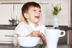 Children and nutrition concept. Smiling delighted small cute kid eats tasty cereals and drinks tea, being in good mood, looks happ. Ily at his mother, sits at stock photos