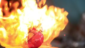 Children old plastic toy rabbit melted from the hot flame of fire. Slow motion video