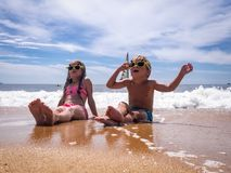 Free Children On The Beach: A Boy And A Girl In Funny Sunglasses Are Sitting On The Seashore In Sea Foam. In The Background A Royalty Free Stock Images - 124899349