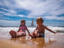 Free Children On The Beach: A Boy And A Girl In Funny Sunglasses Are Sitting On The Seashore In Sea Foam. In The Background A Stock Photography - 125242112