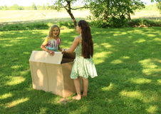 Children opening a box. Barefoot children - two smiling girls opening a paper box Royalty Free Stock Image