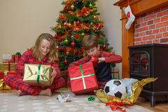 Children opening gifts on Christmas morning. Two children, a boy and a girl, opening their presents on Christmas morning Stock Photography