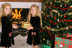 Children opening presents by fireplace. Shot of children opening presents by fireplace Stock Photo